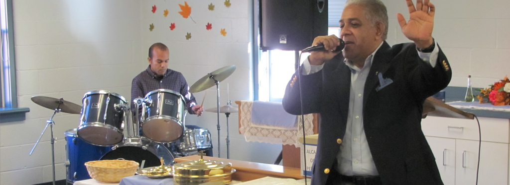 Man singing, with drums in the background