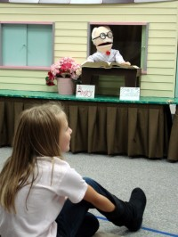 Photo of a young girl watching a puppet show