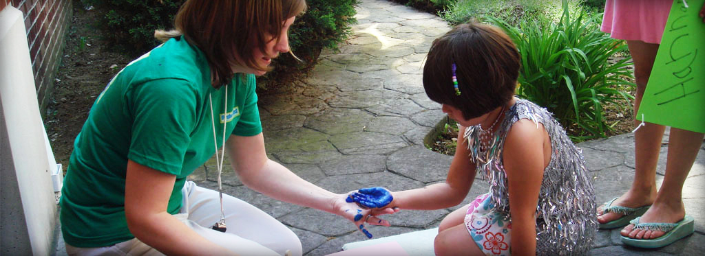 Photo of a woman helping a young girl hand paint