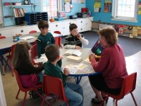 Photo of a group of kids with sunday school teacher in a classroom setting