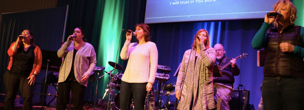 A group of 5 women singing on a stage during worship.